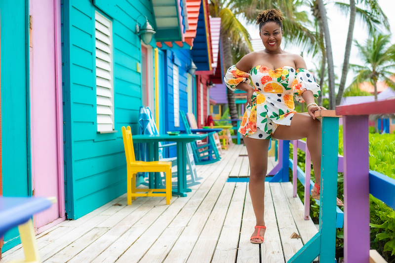 Washington DC based blogger Rogan poses in front of the Compass Point Resort in The Bahamas. Visiting this colourful resort ranks high as one of the best things to do in Nassau.