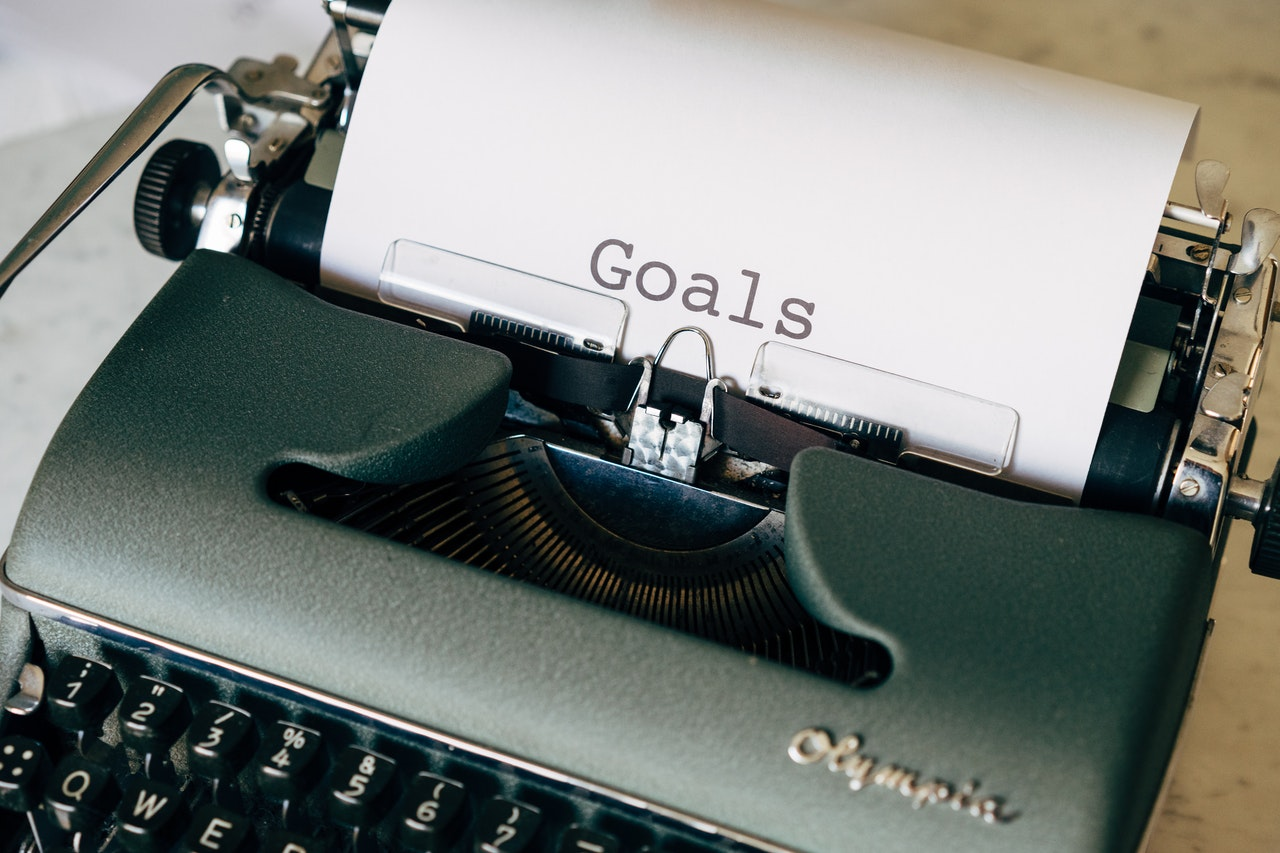 Photo of an old typewriter with the word, goals typed on a sheet of white paper.