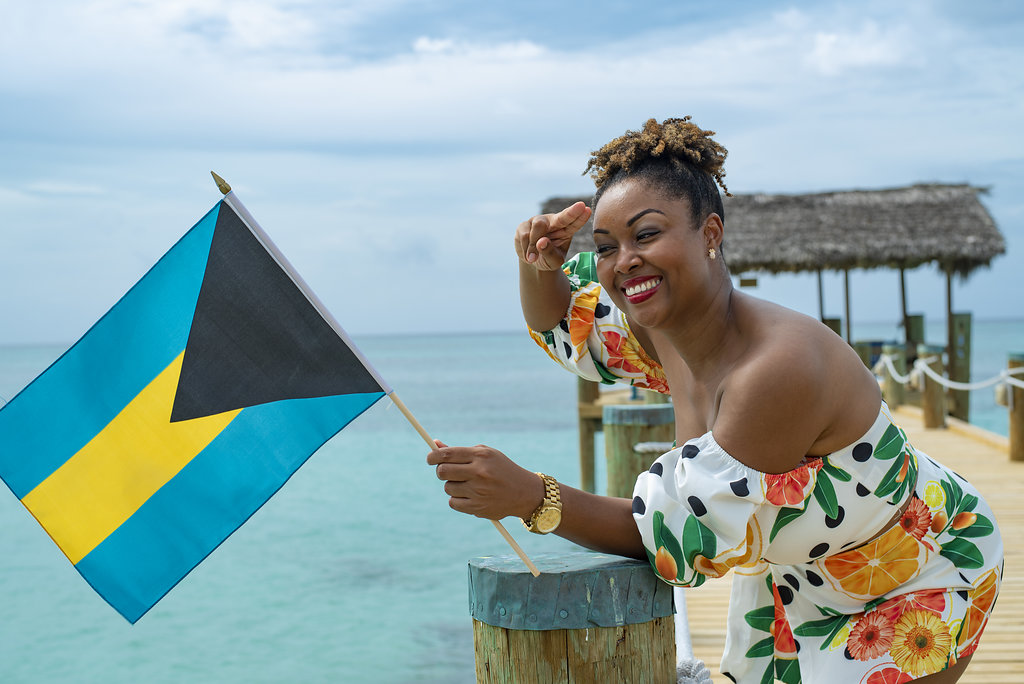 Bahamian Blogger Rogan Smith poses on a beach with a Bahamian flag in her hand. She salutes the flag with her right hand