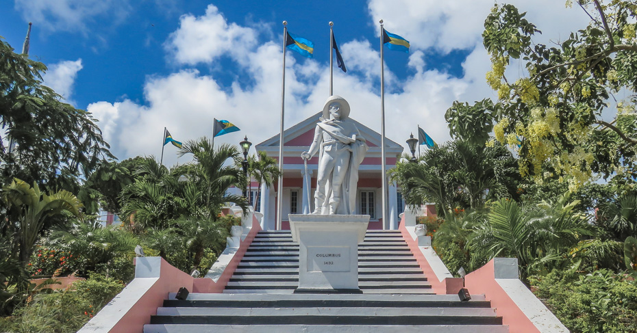 A Christopher Columbus statue stands in front of Government House in The Bahamas. Several Bahamian flags fly in the background and trees surround the statue.