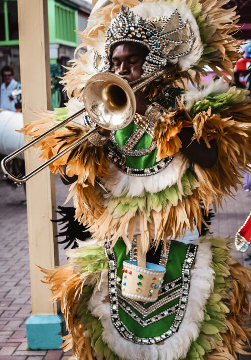 An image of a black Bahamian man in a traditionial junkanoo costume. He is shown blowing a horn.