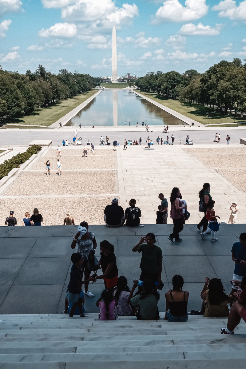Photo of tourists sightseeing at the Lincoln Memorial. You can see the length of the National Mall