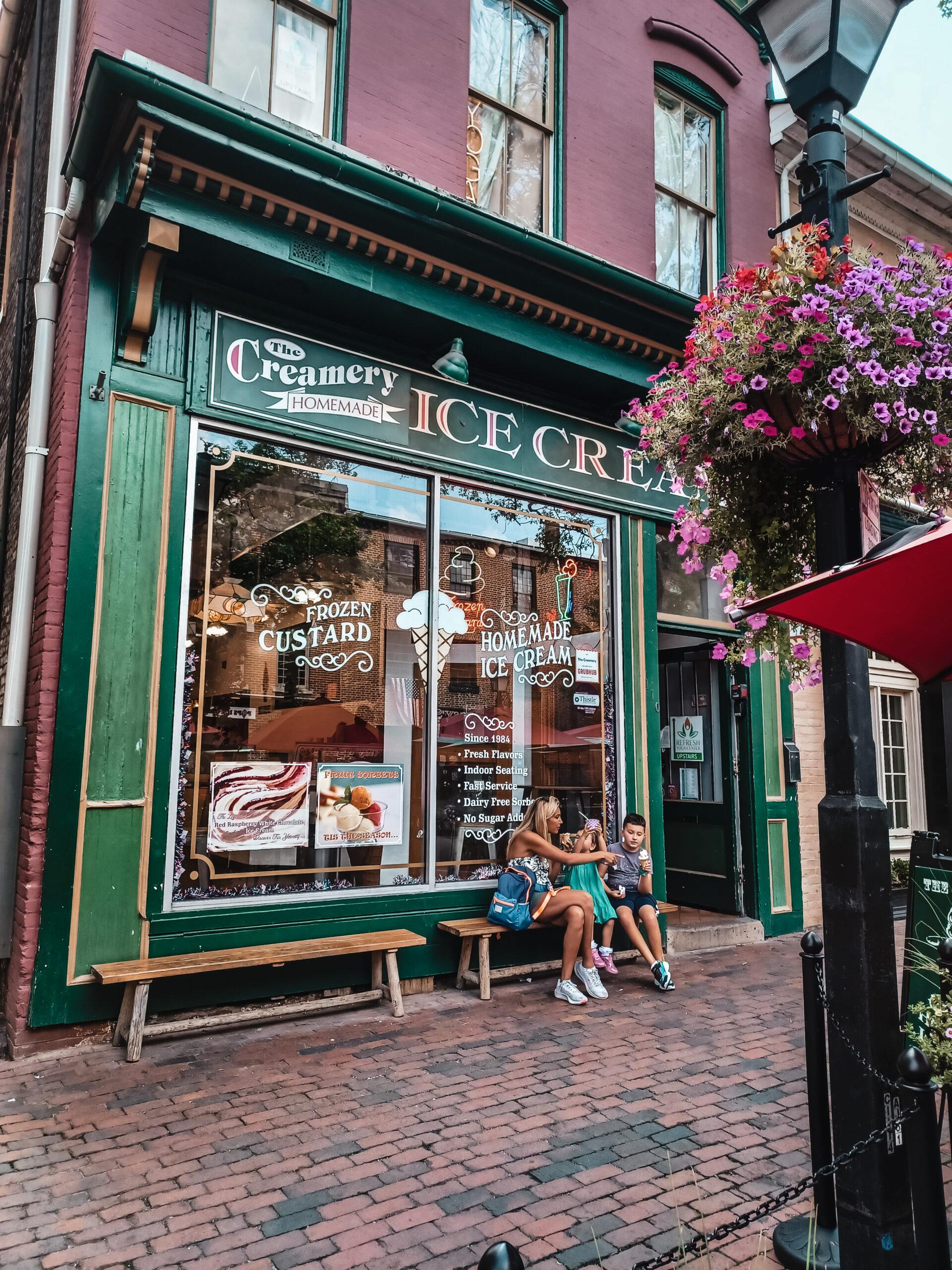 A mother and her children sit in front of an ice cream shop in Alexandria Virginia