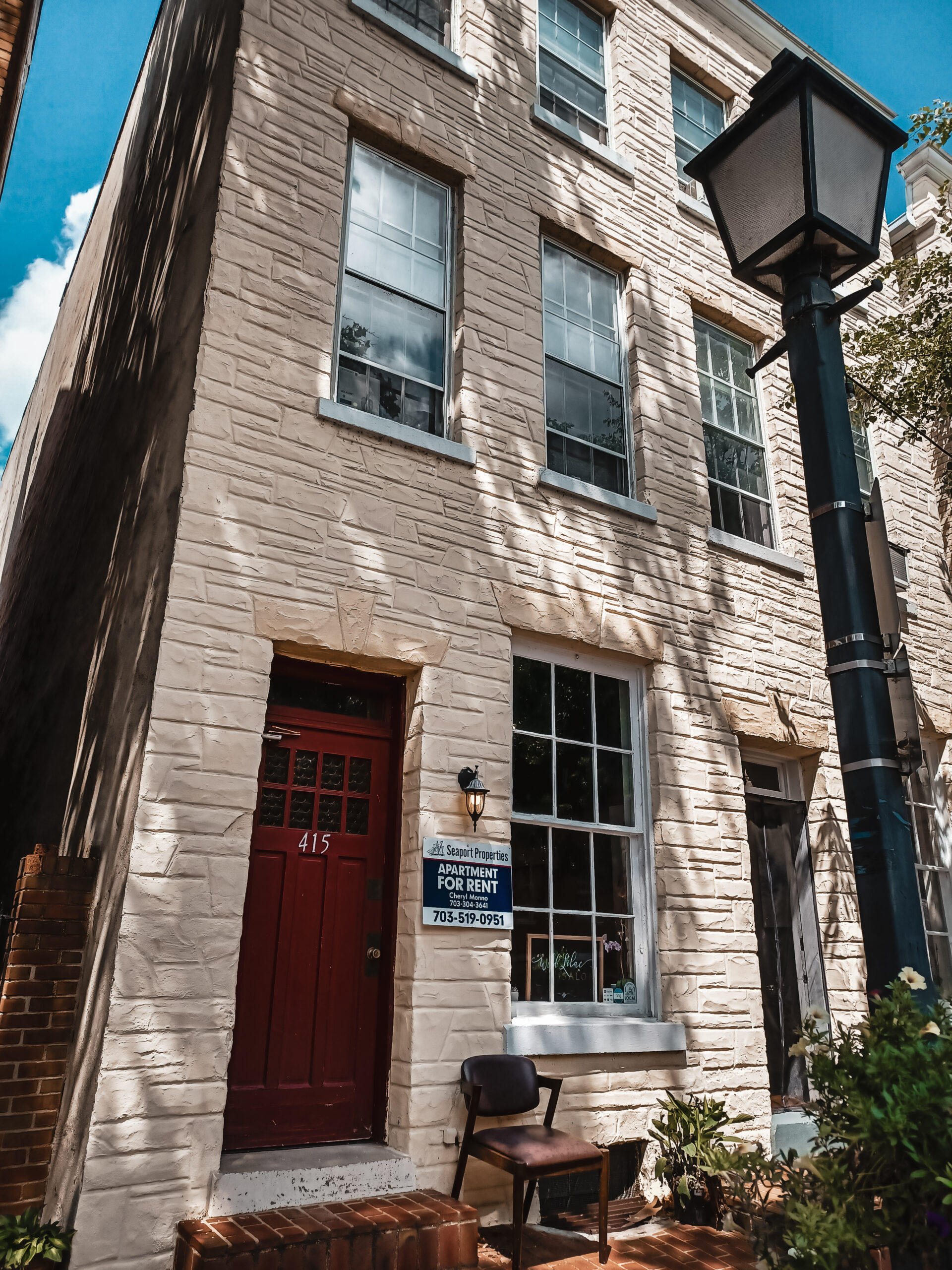 Photo of a beige brick building with a red door. A for rent sign hangs on the light. The building is in Alexandria Virginia
