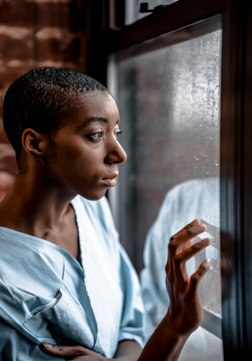 Black female hospital patient stares out of window photo by klaus nielsen