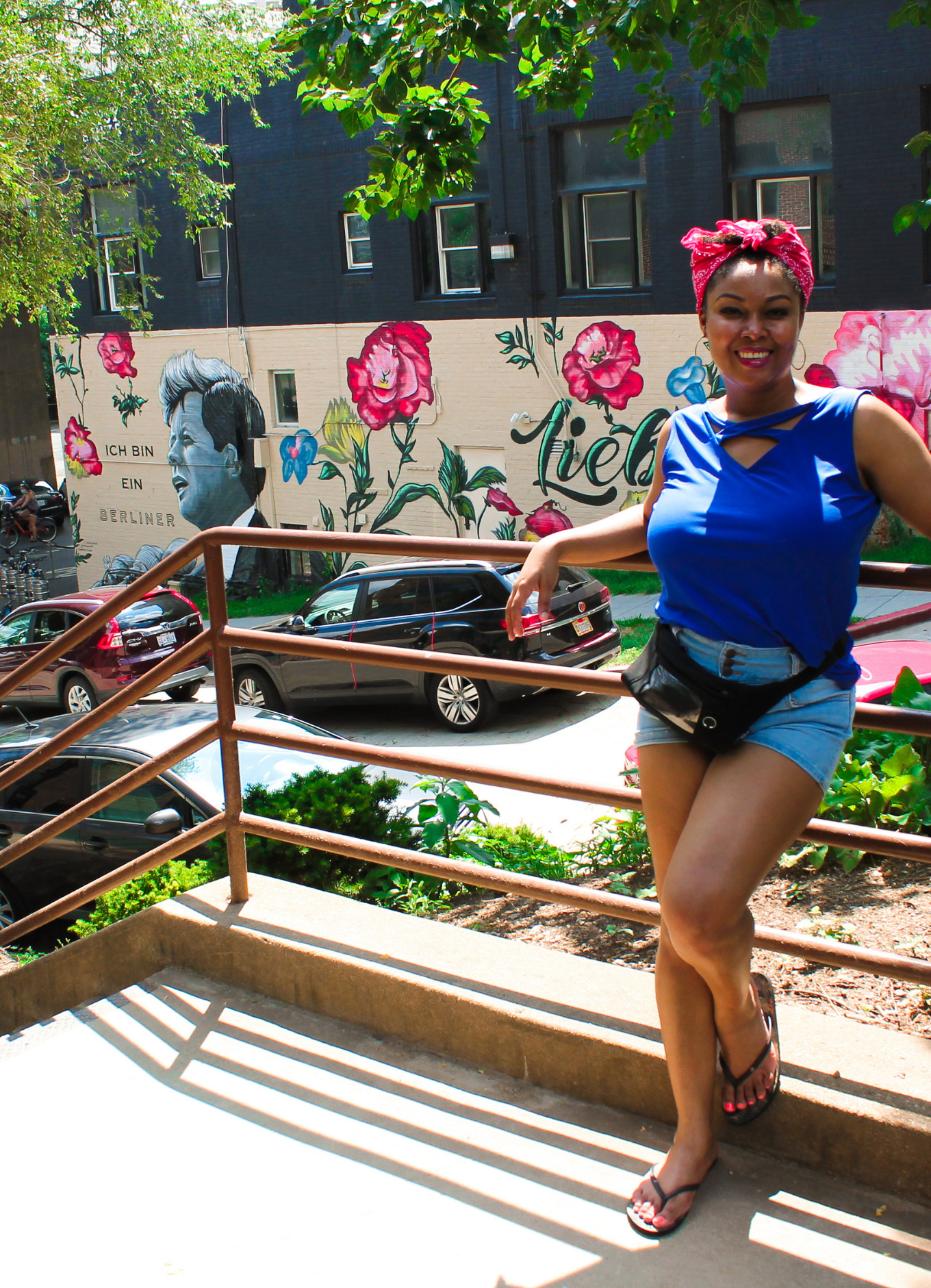 Blogger Rogan Smith wears a red bandana and a blue shirt. She poses against a rail with a mural of John F Kennedy in the background