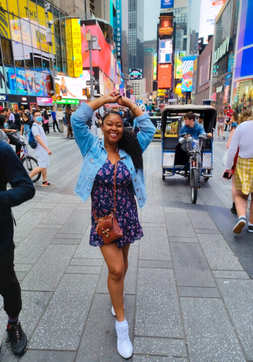 This Bahamian Gyal blogger Rogan Smith smiles in Times Square New York City
