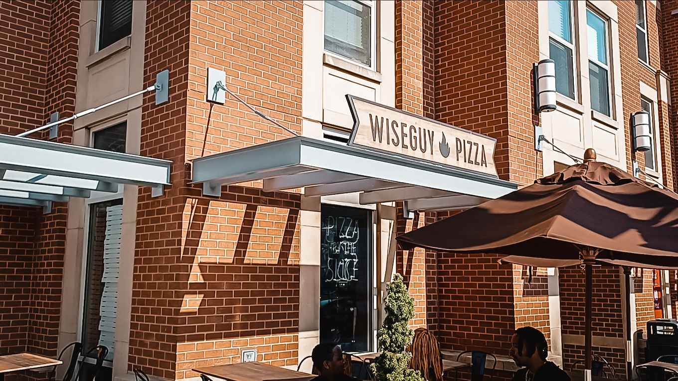 Wiseguy Pizza exterior family sits to eat