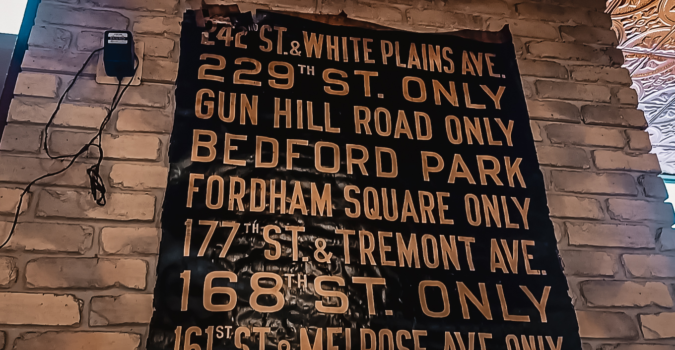 A black sign hangs on Wiseguy Pizza's wall showing the names of popular areas in New York City