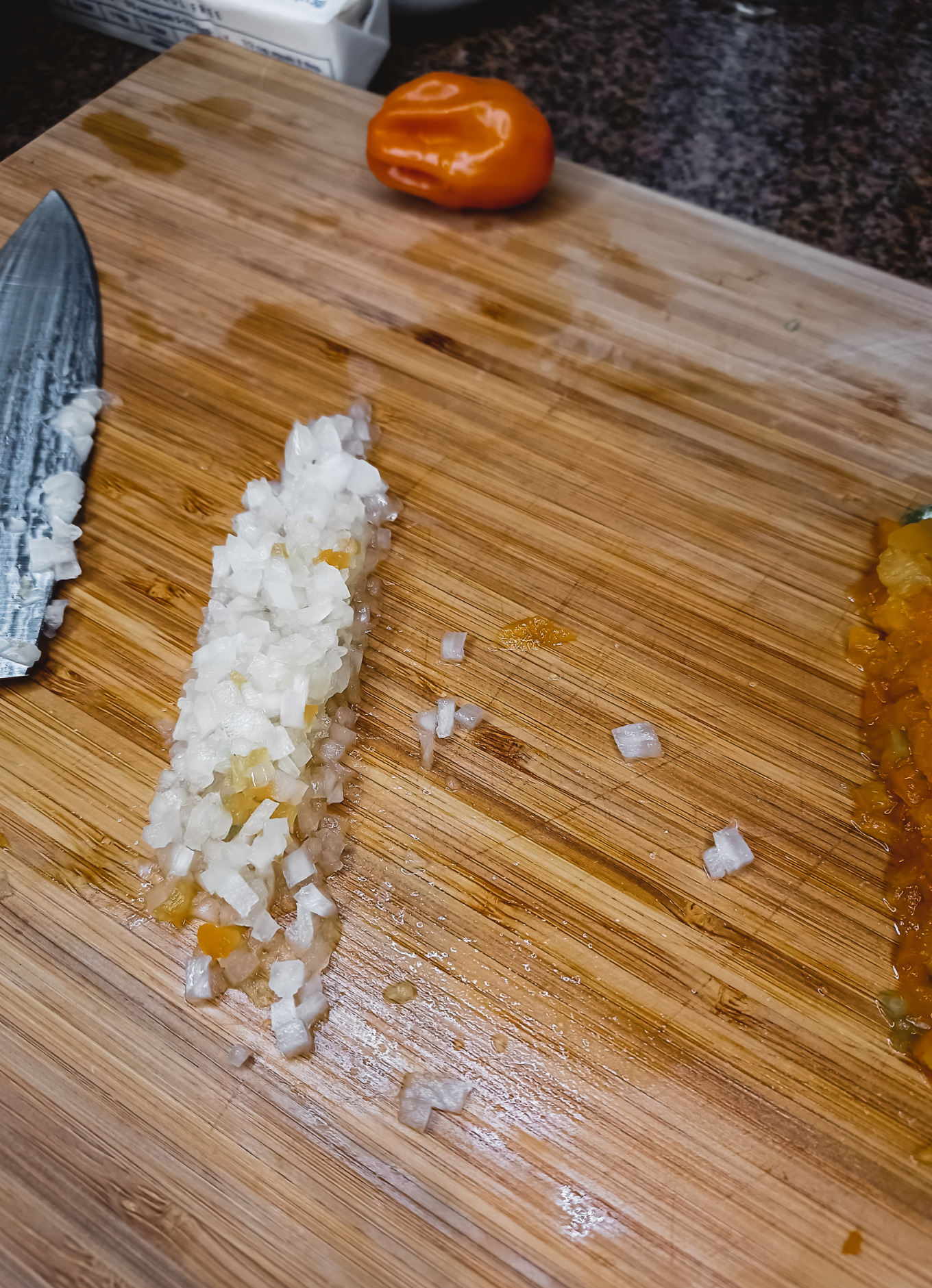 A cutting board with a knife, habanero pepper and onion.