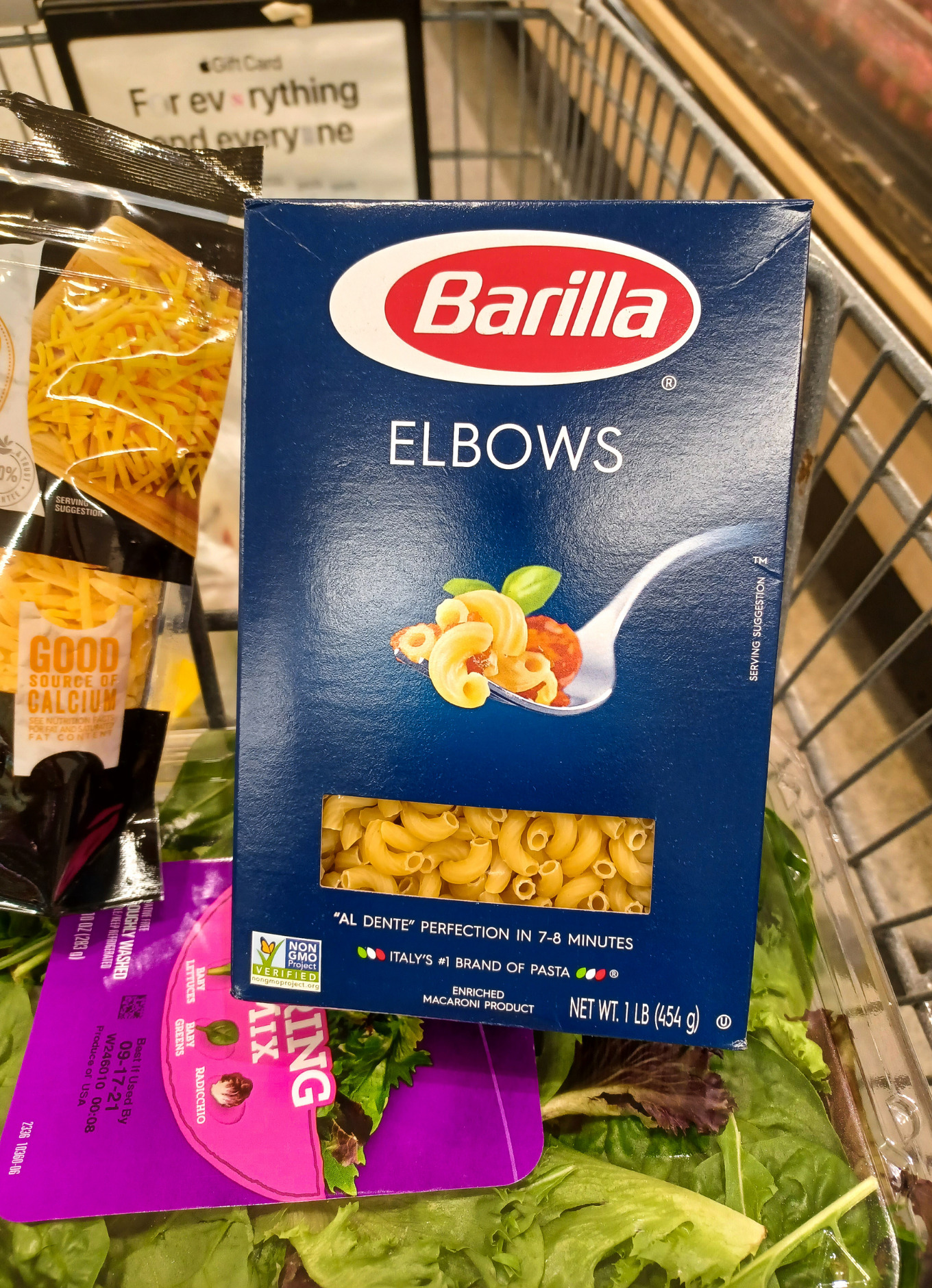 A box of Barilla elbow macaroni in a grocery cart