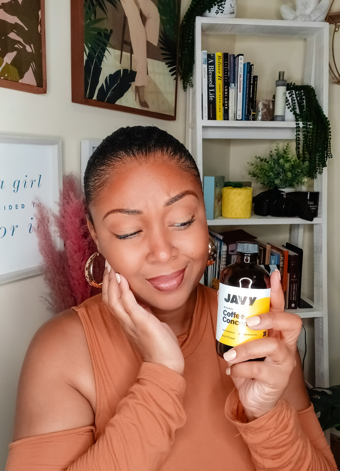 Black blogger holds Javy concentrated cofeee in her hand and holds her face