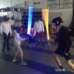 Photo of using light sabers at camp