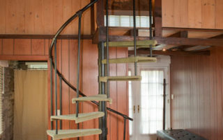 Studio spiral staircase leading to loft bedroom with a king bed