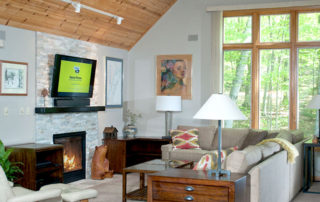 Bluffside's living room area with couch, chair, fireplace and TV