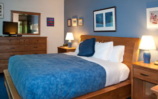 One of the Bluffside bedrooms with bed, lamps, dresser and TV