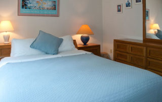 One of the Bluffside bedrooms with bed, lamps, dresser and mirror