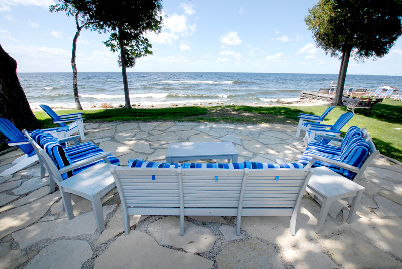Deck chairs on stone patio overlooking the bay