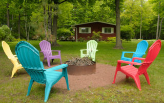 Colorful lawn chairs surrounding fire pit near Falun House