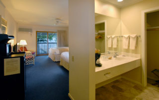 Interior of a Shoreside Motel room with bathroom, two beds, and chairs