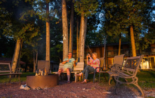 Two people sitting on benches by a fire pit in front of Beachhouse