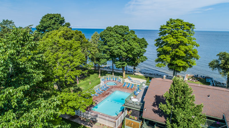 Aerial view of outdoor pool surrounded by trees with bay in the background