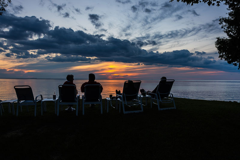 Resort guest relaxing around a fire on chairs and benches by the water at sunset