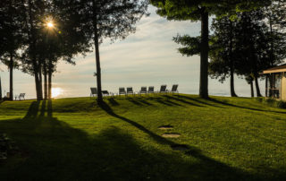 Line of lawn chairs along the shore with sunset over the water