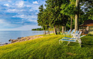 Line of lawn chairs along the shore with blue sky and water