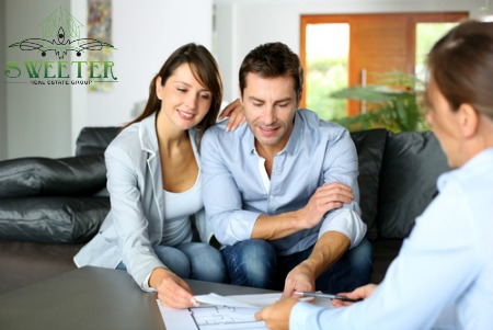 Couple signing papers with agent