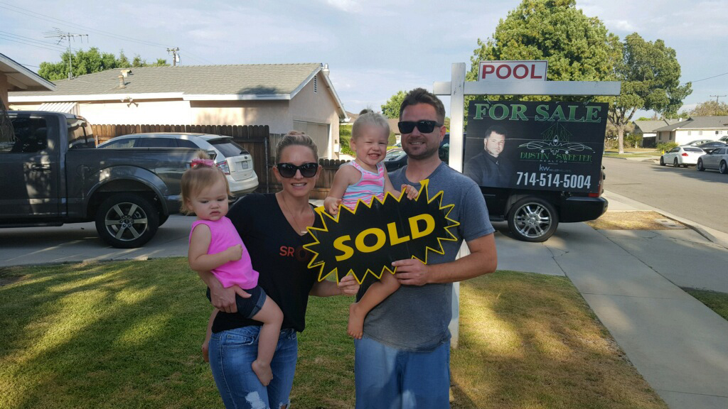 Sellers with the sold sign standing in front of the house