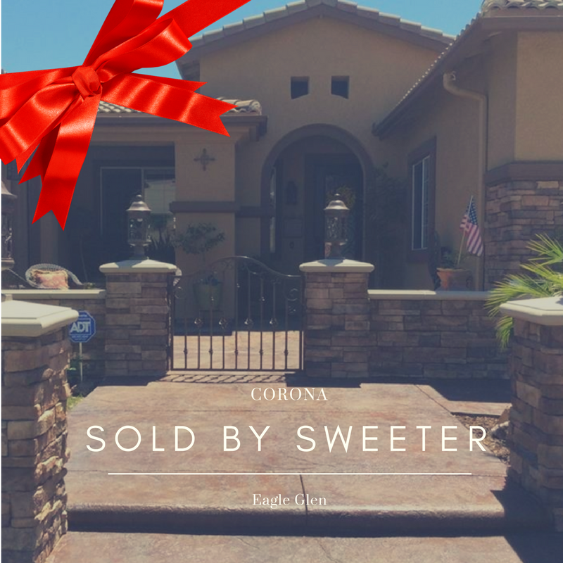 """Front view of home with red bow and caption """"Sold by Sweeter"""""""