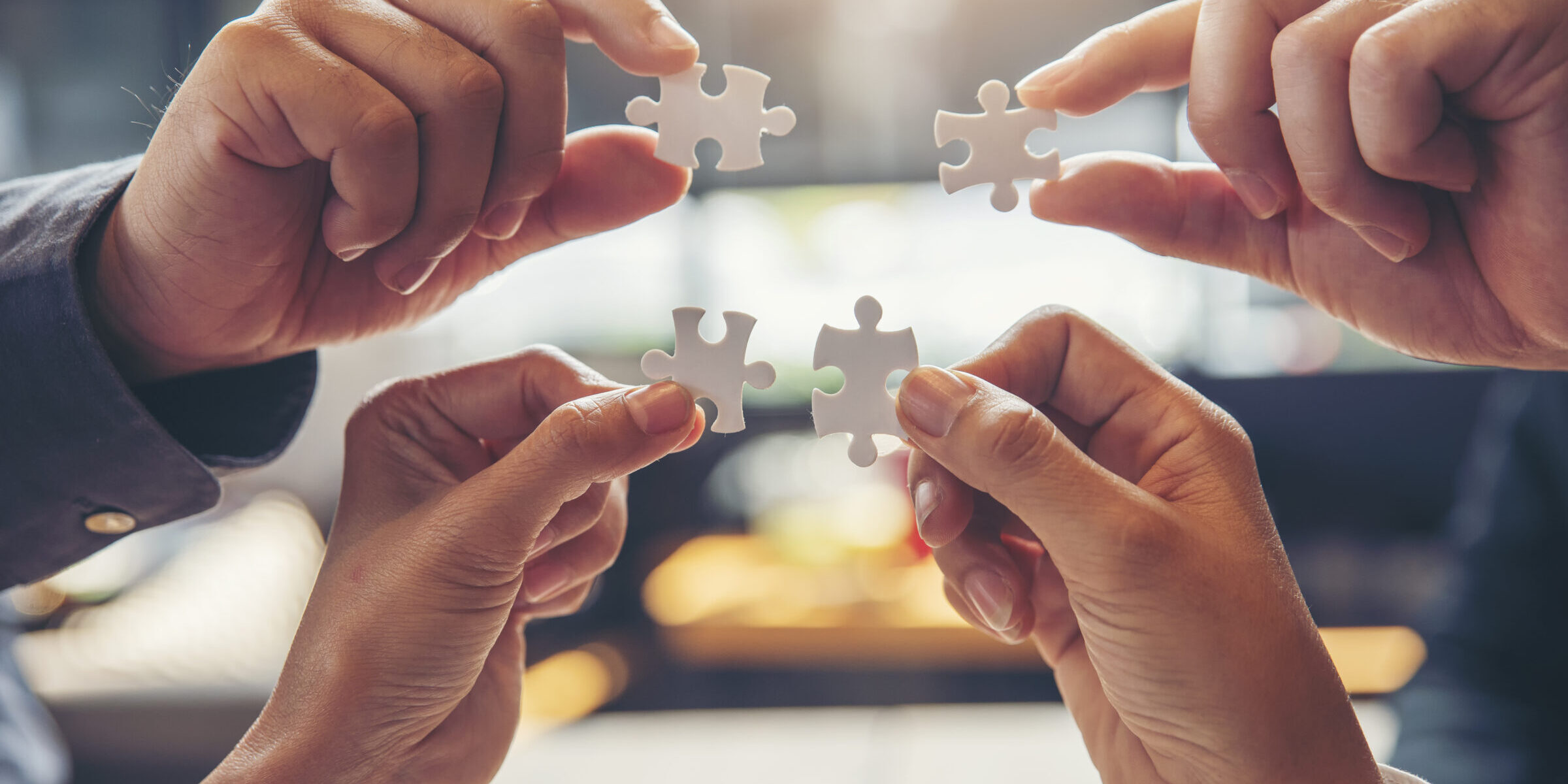 Strategy and Solution Business Concept.Group of Business people holding piece of jigsaw puzzle to solution problem on wooden desk.Professional Businessman and Partnership meeting in office.