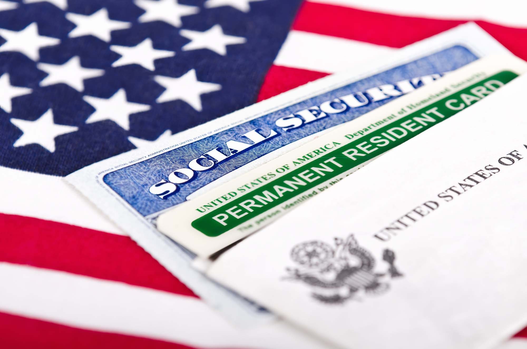 EB-5 Program United States of America social security and green card with US flag on the background. Immigration concept. Closeup with shallow depth of field.