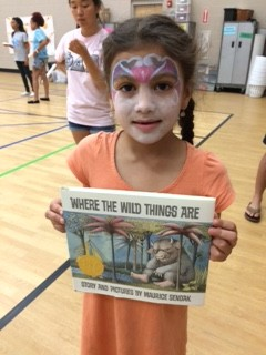 A student shows off the book she won during the book walk!