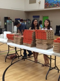 MGC members serve pizza to guests.