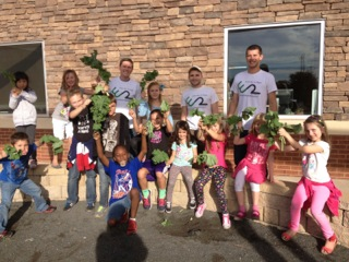 Week 8. Students proudly show off their kale harvest. The Garden Your Own Growth team collected the kale and made kale chips for the students to eat or take home.