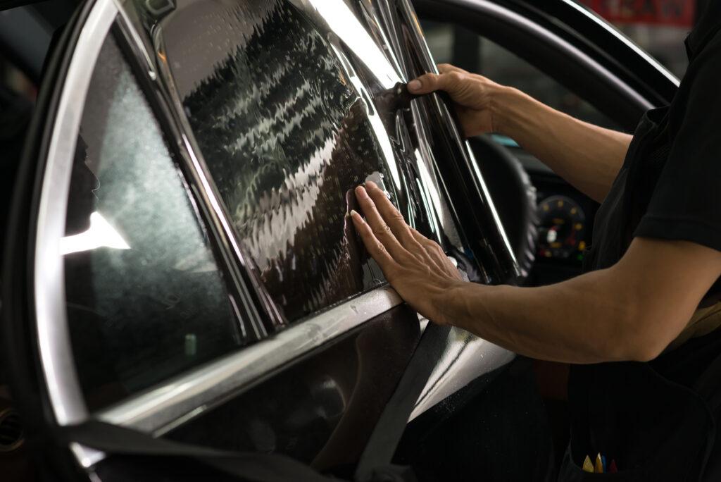 Crew applying dark tint on customer's car