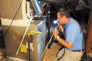 Blake, the owner of TCHI, examining an air conditioning unit