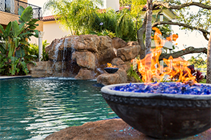 A completed pool with a firepit and waterfall