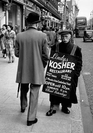 A sandwich-man advertising a Kosher restaurant in London's Oxford Street. Original Publication: Picture Post - 5884 - The Dandy Comes Back To W1 - pub. 1952 (Photo by Thurston Hopkins/Getty Images) format portrait;clothing;sign;couple;male;back view;elderly;Advertising;Eating Out;Europe;Britain;England;M 38164;M/CLO/1950-59/MENS/1952