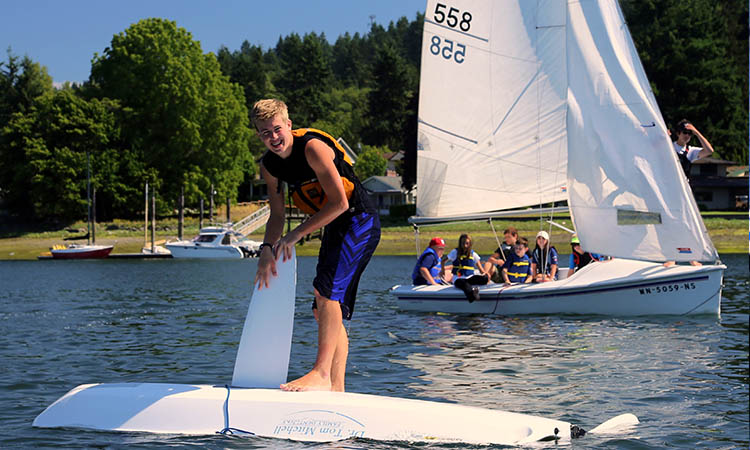 Summer camp sailing lessons on how to turtle a boat