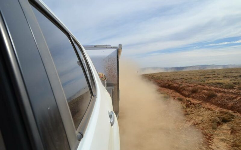 action dust shot of camper on dirt road