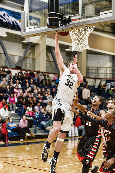 Two West players are dunked on by Senior Kevin Waterman