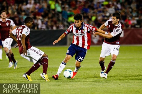 May 25th, 2013 - Chivas USA midfielder Carlos Alvarez (20) dribbles the ball against the defense by Colorado Rapids midfielder Nathan Sturgis (24) and forward Deshorn Brown (26) in the second half of the MLS match between Chivas USA and the Colorado Rapids at Dick's Sporting Goods Park in Commerce City, CO