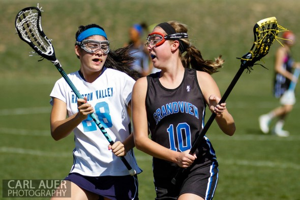 April 27th, 2013: Grandview Wolves senior Taylor Arnold (10) attempts to carry the ball past the defense by Ralston Valley Mustangs freshman Olivia Sandoval(28) in the game at Ralston Valley High School on Saturday morning in Arvada, Colorado