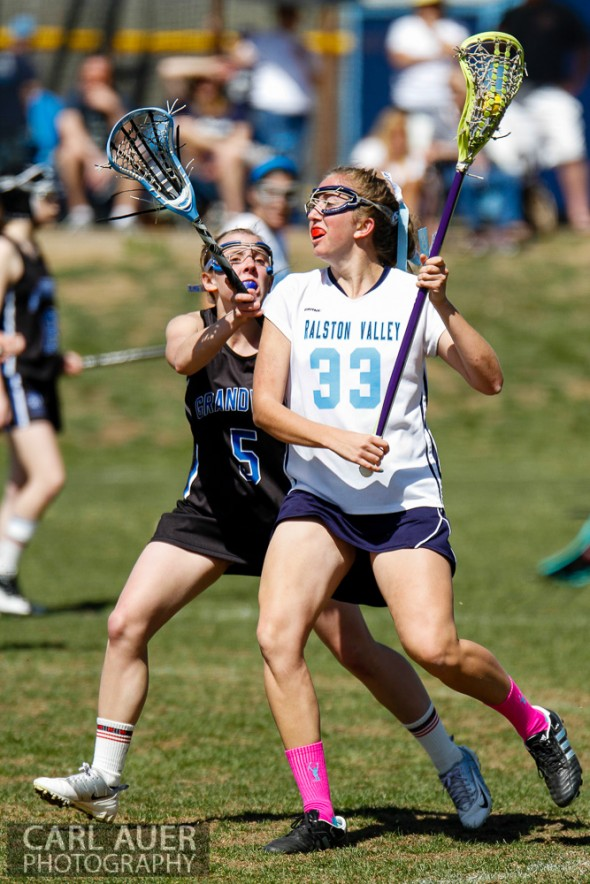 April 27th, 2013: Ralston Valley Mustangs senior Jenny Adams (33) attempts to make a move with the ball past the defense by Grandview Wolves sophomore Katie Sengenberger (5) in the game at Ralston Valley High School on Saturday morning in Arvada, Colorado