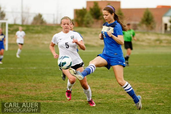 April 29th, 2013:  Wheat Ridge Farmers senior defender Kayla Blosser (5) kicks the ball away from D'Evelyn Jaguars sophomore Taylor Hager (5) in the game at the North Area Athletic Complex in Arvada, Colorado
