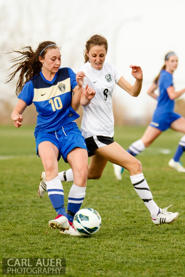 April 29th, 2013:  Wheat Ridge Farmers senior midfielder Macee Broer (10) passes the ball past the defense by D'Evelyn Jaguars senior Olivia Hoffman (8) in the game at the North Area Athletic Complex in Arvada, Colorado