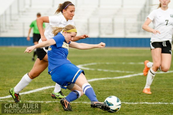 April 29th, 2013:  Wheat Ridge Farmers senior midfielder Elise Boisnard (12) fires a shot off past the defense by D'Evelyn Jaguars senior Kendall MacCagnan (19) in the game at the North Area Athletic Complex in Arvada, Colorado